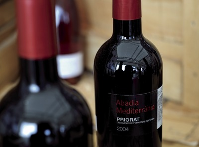 D.O.Q. Priorat. Abadia Mediterrània red wine amongst wooden crates and bottles (© Marc Castellet)