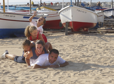 Family taking a photo next to some fishing boats on the beach of Calonge (© Ajuntament de Calonge i Sant Antoni)