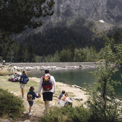Family hiking next to a lake in the Aigüestortes National Park, Pallars Sobirà. (© Jordi Pou)