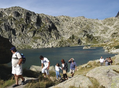 Group of hikers walking up a path next to a lake in the Aigüestortes National Park, Pallars Sobirà. (© Jordi Pou)