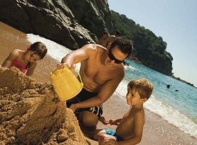 Father and children playing in the sand of the beach of Lloret de Mar (© Joan Vendrell Marce)