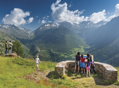 Group of people enjoying the views of the head of the Vall de Cardós from the Corbiu Viewpoint (Alt Pirineu Natural Park). There is a panel with additional information about the geography, flora and fauna of the natural park. (© Òscar Rodbag)